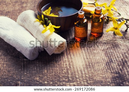 Spa setting. Essential aroma oil , water in bowl, towels, yellow flowers on aged wooden background. Selective focus. Place for text. Toned image.