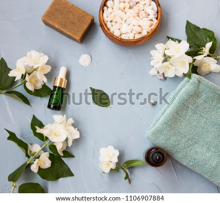 Spa setting flatlay with bath salt, jasmine oil bottle and flowers, towel and natural soap. Spa and wellness still life