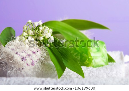 Spa setting of white towels, wisp, green soap and lilies of the valley