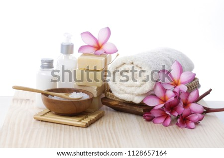 spa setting with rolled towel, salt in bowl, soap, bottle oil, frangipani