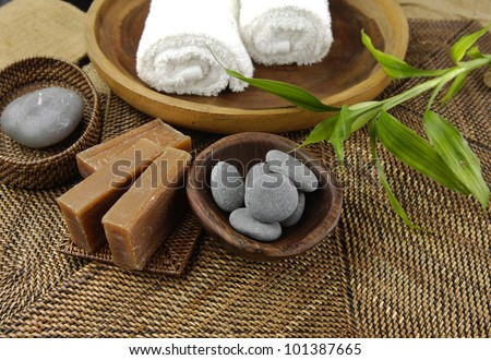Spa setting with roller towels and stones in bowl and bamboo plant , soap