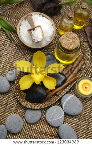 Spa setting with salt in bowl and candle ,massage oil ,orchid