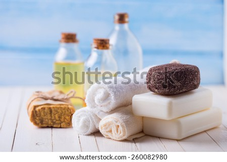 Spa setting with soap, towels, pumice and aroma oil on  painted wooden boards. Selective focus is on towels.