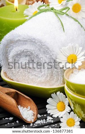 Spa setting with towel, sea salt and fresh daisies