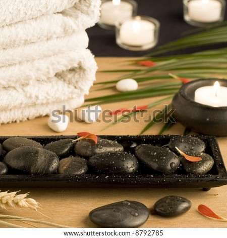 Spa setting with white towels, pebbles, candles and palm leaf