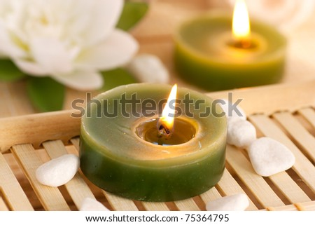 Spa setting withcandles, waterlily and pebbles