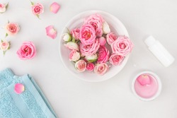 Spa settings with roses. Fresh roses and rose petals in a bowl of water and various items used in spa treatments