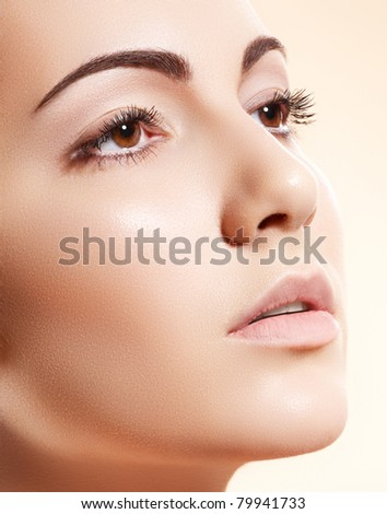Spa, skincare, wellness & health. Close-up portrait of beautiful female model face with purity health skin & light make-up on bright beige background.