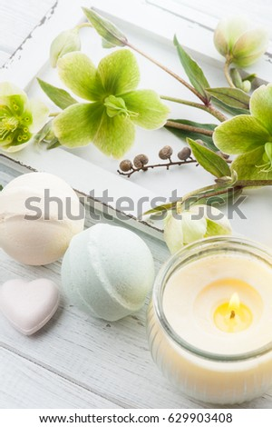 SPA still life, bath bombs and lit candle on white wooden background