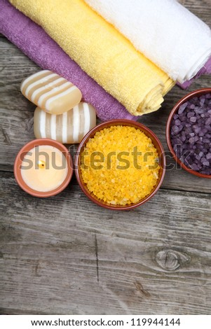 Spa still life: soap, salt for baths, a flower and towels on a wooden background
