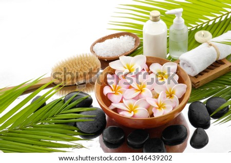 Spa still life with black stones and candle, salt with frangipani in bowl ,roller on bowl, bottle, oil,palm