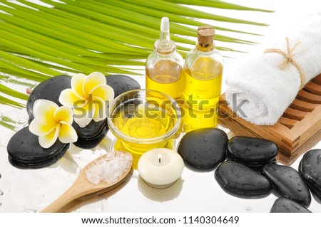 Spa still life with black stones and frangipani,, candle, salt in bowl  bottle, oil, palm