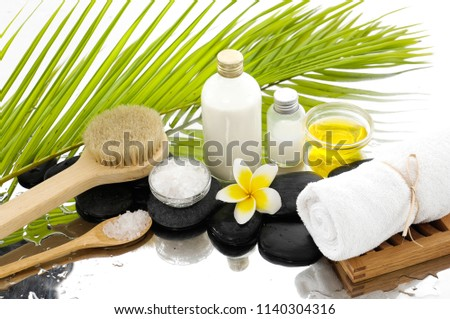 Spa still life with black stones and frangipani,, candle, salt in bowl ,towel ,bottle, oil,palm