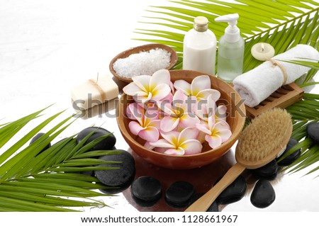 Spa still life with black stones and frangipani,, candle, salt in spoon, bottle, oil,palm,brush,