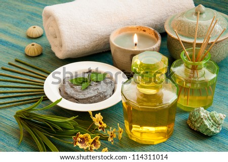 Spa still life with Bottle of aromatic essence oil, organic scrub, bottle of fragrance reeds diffuser  orchid flower, towel, candle, incense and shells.
