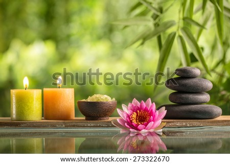 Spa still life with burning candles,zen stone and salt reflected in a serenity pool
