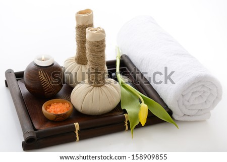 spa still life with spa herbal balls candlestick tulip stones and salt in wooden bowl and white towel over white