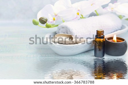 Spa still life with towel,white orchid,sea salt,bath oil and candle on water reflection