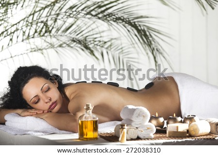 Spa Stone Massage. Beautiful Woman Getting Spa Hot Stones Massage in Spa Salon.