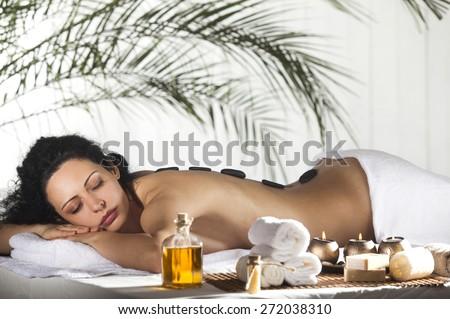 Spa Stone Massage. Beautiful Woman Getting Spa Hot Stones Massage in Spa Salon.