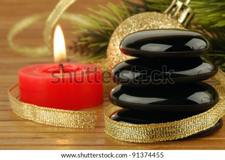 Spa stones, christmas ball and candle with golden ribbon. Focus on a stones.
