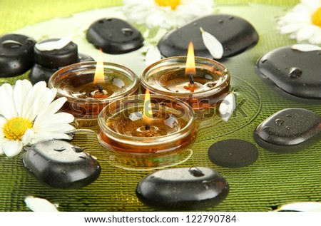 spa stones with flowers and candles in water on plate