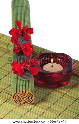 Spa stones with red petals and a candle