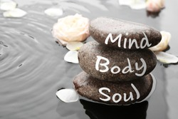 Spa stones with words Mind, Body, Soul and rose petals in water, space for text. Zen lifestyle