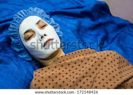 spa teen girl applying facial clay mask. Beauty treatments
