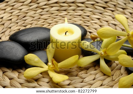 Spa theme- candle and zen stones with orchid on woven mat