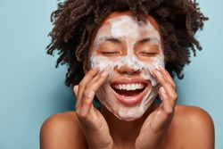 Spa, therapy and beauty concept. Satisfied black woman washes face with white soap, has cleansing foam, purification of face, cleans pores, shows bare shoulders, isolated over blue studio wall