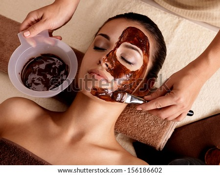 Spa therapy for young woman having facial mask at beauty salon indoors