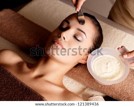 Spa therapy for young woman receiving facial mask at beauty salon indoors