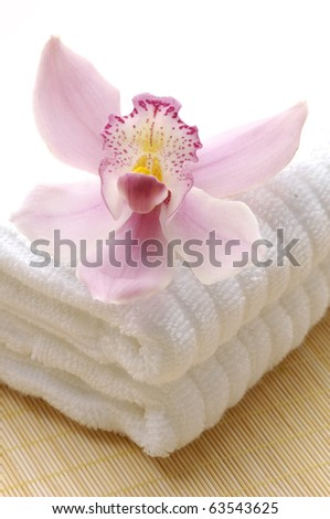 Spa towels with pink orchid on mat