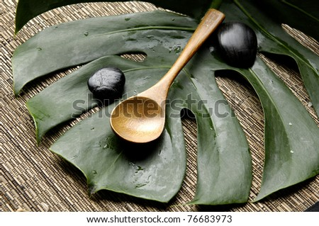Spa treatment background-spoon and green leaf on bamboo mat