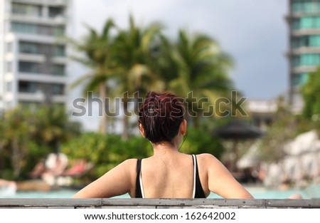 Spa vacation retreat woman relaxing at luxury travel resort. Happy blissful asian young woman in bikini in meditation enjoying summer sun and tanning during holidays .