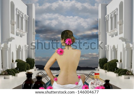 Spa wellness woman sitting with a bare back in a towel in a white hotel and relax