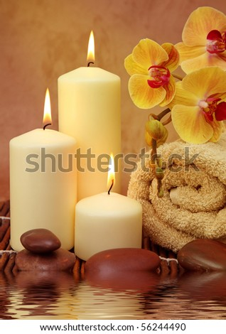 Spa with white candles on a brown backdrop