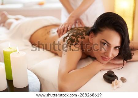 Spa Woman. Brunette Getting a Marine Algae Wrap Treatment in Spa Salon