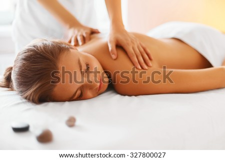 Photo of Spa woman. Female enjoying relaxing back massage in cosmetology spa centre. Body care, skin care, wellness, wellbeing, beauty treatment concept.