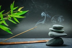 Spa zen basalt stones and green bamboo leaves on black background. The concept of wellness, relaxation, massage and well-being. Still life background. Harmony and balance.