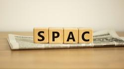 SPAC, special purpose acquisition company symbol. Wooden cubes with word 'SPAC' on beautiful white background, copy space. Newspaper. Business and SPAC, special purpose acquisition company concept.