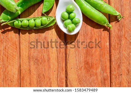 space of peas beans,green peas beans on wood,wooden table on green peas beans,peas beans on wood,spoon on wood table and healthy peas,peas close up view