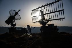 Space radar antenna on sunset. Silhouettes of satellite dishes or radio antennas against night sky. Creative artwork decoration. Selective focus
