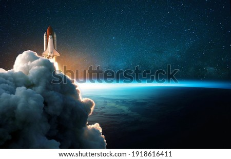 Space rocket lift off into cosmos with smoke and blast on a background of the blue planet earth. Spacecraft flies in space with a starry sky near the planet. Successful start of the mission