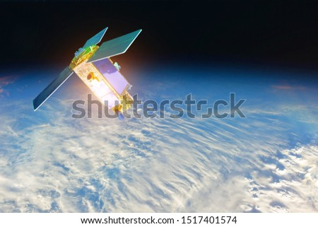 Space satellite at the border of day and night terminator orbiting the earth during sunset and bright rays lights sun reflected from solar panels. Elements of this image furnished by NASA