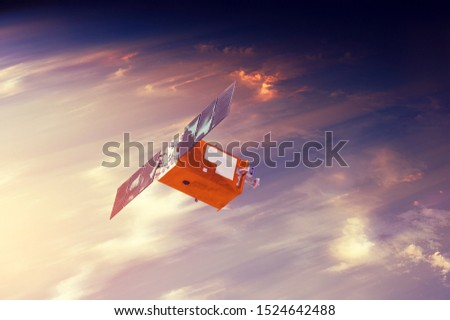 Space satellite flying in orbit over sunset clouds orbiting Earth. Bright light from the sun and glare. Elements of this image furnished by NASA