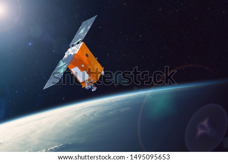 Space satellite orbiting Earth low polar orbit. Bright light from the sun and glare in the frame. Elements of this image furnished by NASA