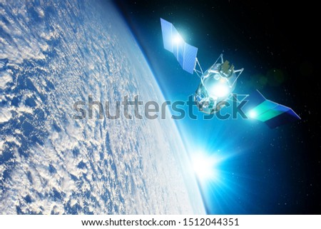 Space satellite orbiting the earth during sunset and bright rays lights sun reflected from solar panels. Elements of this image furnished by NASA