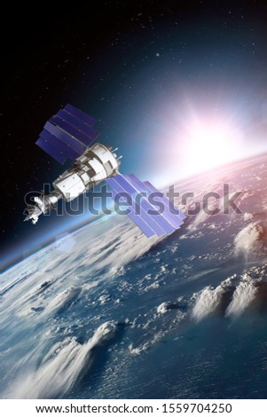 Space satellite solar panels orbiting the earth during sunset and bright rays lights. Elements of this image furnished by NASA